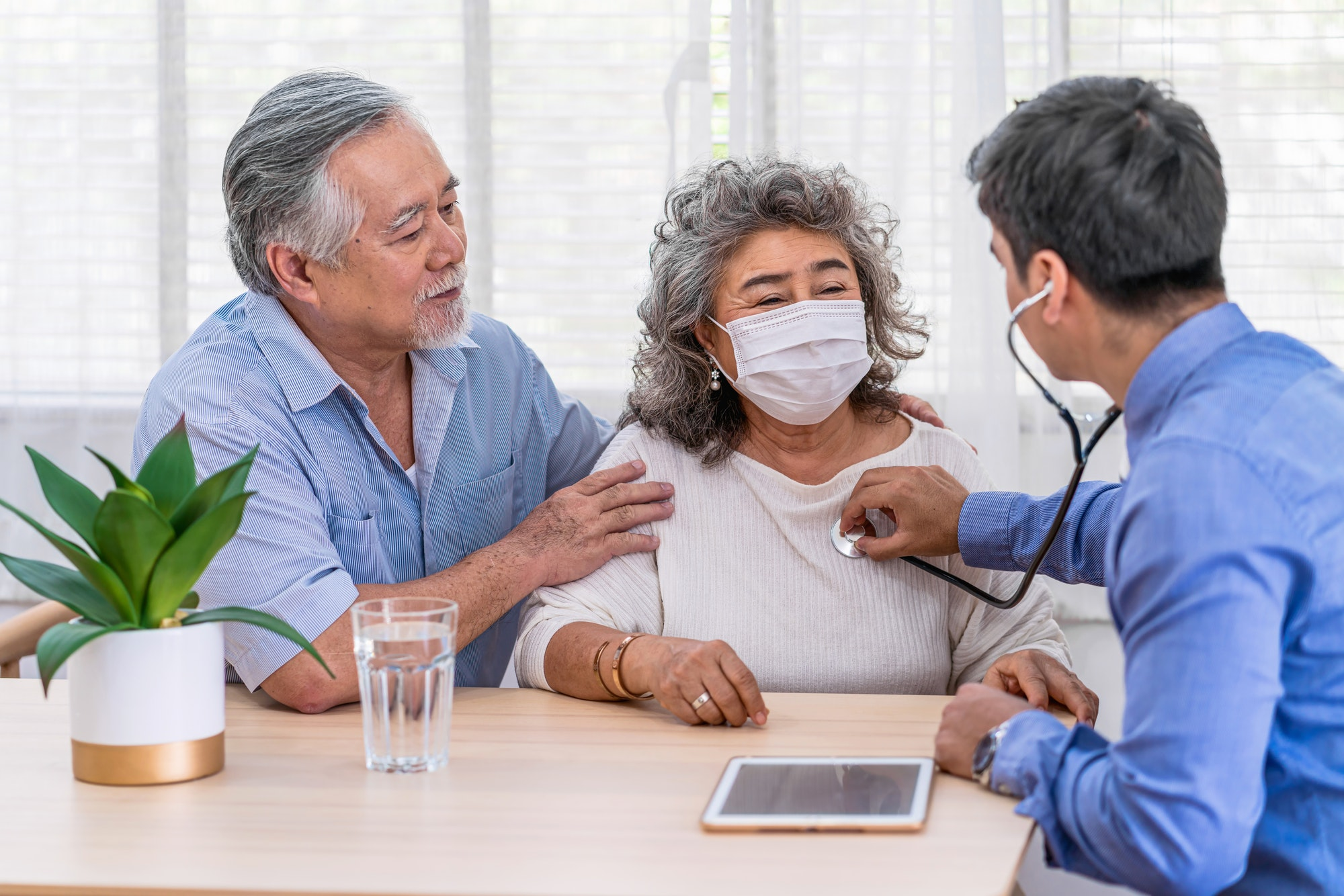 Doctor using stethoscope for auscultate Asian grandparent patient in house, service Life insurance